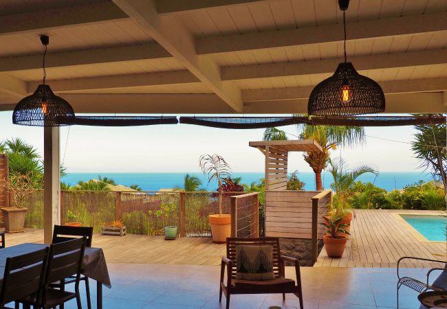 Spacieuse terrasse avec vue sur l'océan et la piscine